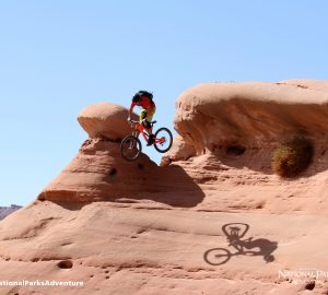 Mountain biker Eric Porter jumps over a mushroom boulder in Moab, Utah. Courtesy of MacGillivray Freeman Films. Photographer: Barbara MacGillivray ©VisitTheUSA.com