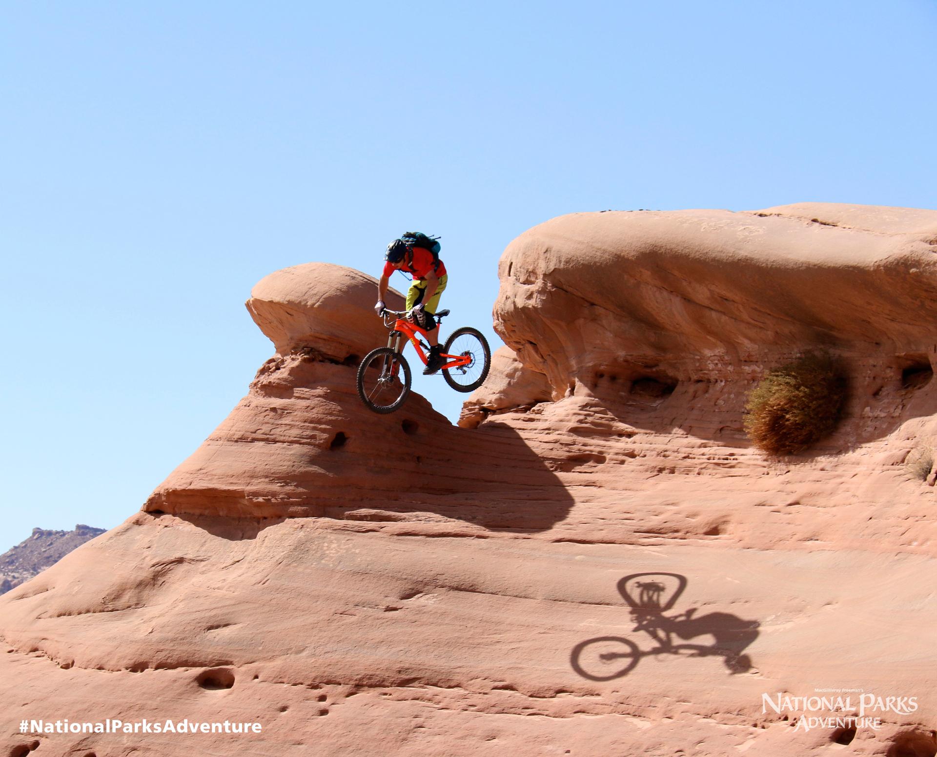 Mountain biker Eric Porter jumps over a mushroom boulder in Moab, Utah. Courtesy of MacGillivray Freeman Films. Photographer: Barbara MacGillivray ©VisitTheUSA.com